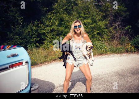 Portrait of woman in sunglasses carrying pugs on street - Stock Photo