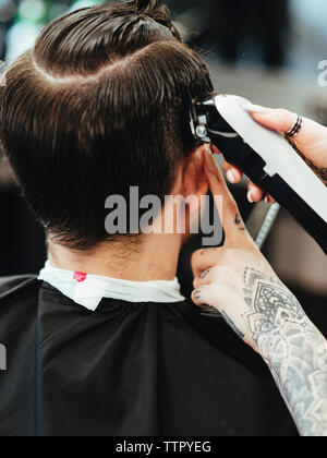 Cropped hands of female hairdresser cutting customer's hair in salon - Stock Photo