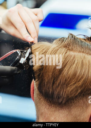 Cropped hands of female beautician cutting customer's hair in salon - Stock Photo