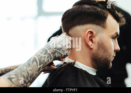 Cropped hands of hairdresser cutting customer's hair in salon - Stock Photo