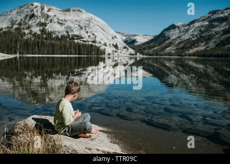 Side view of boy sitting on rock by lake against mountains at Yosemite National Park - Stock Photo