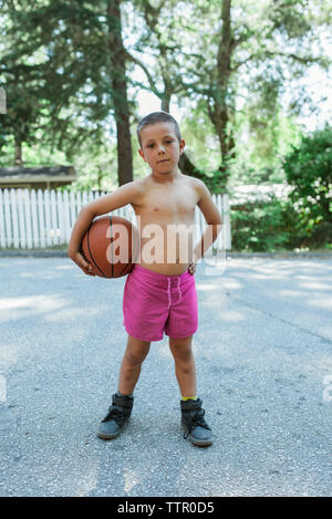 Portrait of shirtless boy holding basketball while standing on footpath against trees at park - Stock Photo