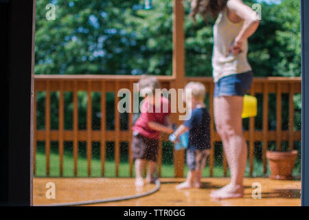 Low section of mother with children in porch seen through glass door - Stock Photo