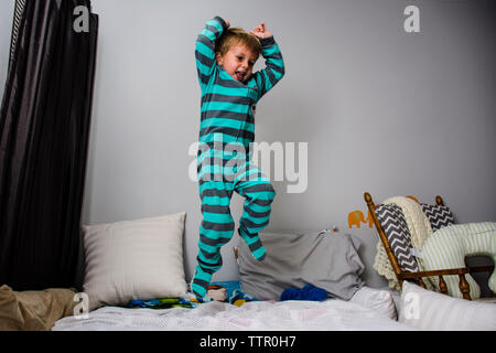 Playful boy jumping on bed at home - Stock Photo