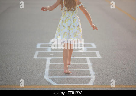 Low section of girl playing hopscotch on footpath - Stock Photo