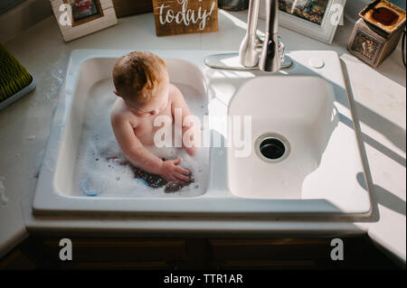 High angle view of shirtless baby boy sitting in kitchen sink at home - Stock Photo