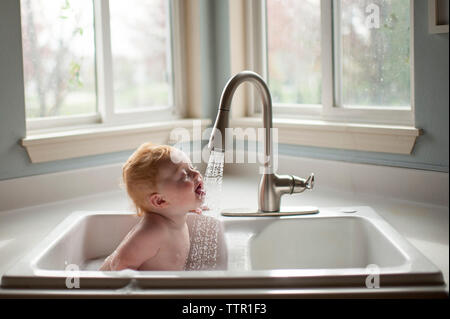 Cute baby boy sticking out tongue under running water from faucet in kitchen sink - Stock Photo