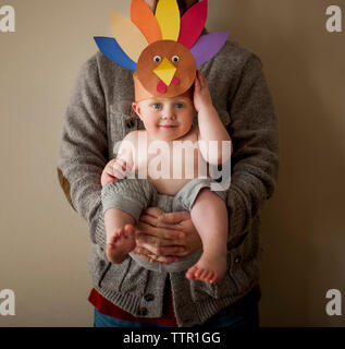 Portrait of cute shirtless son wearing colorful paper headdress while being carried by father against wall at home - Stock Photo