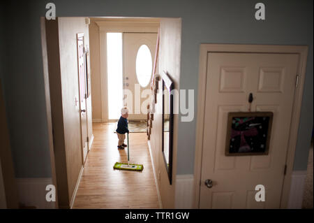 Baby boy wiping hardwood floor with mop at home - Stock Photo