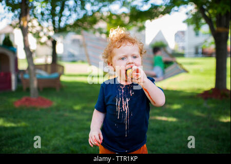 Cute baby boy eating ice cream while standing on grassy field at yard - Stock Photo