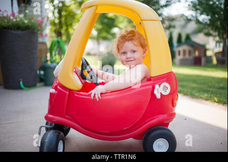 Portrait of cute shirtless baby boy sitting in toy car at backyard - Stock Photo
