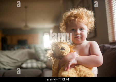 Portrait of cute shirtless baby boy holding stuffed toy in living room at home - Stock Photo