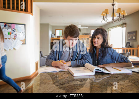Mother teaching son on table at home