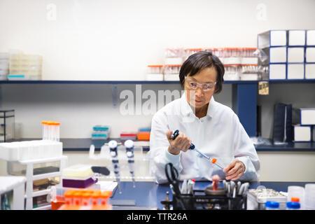 Senior female scientist using pipette in laboratory - Stock Photo