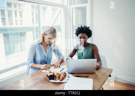 Businesswomen working at conference table in creative office - Stock Photo