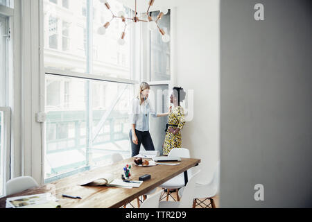 Side view of businesswomen talking while standing by window in board room - Stock Photo
