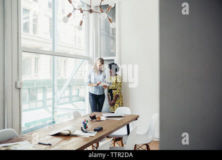Businesswomen reading book while standing by window in board room - Stock Photo