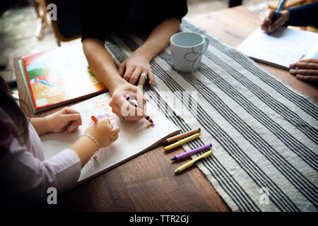 High angle view of mother teaching drawing to daughter on table - Stock Photo