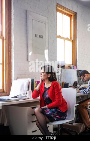 Thoughtful businesswoman looking through window while sitting in office - Stock Photo