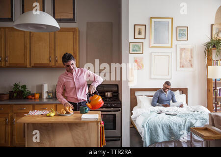 Homosexual man pouring coffee in cup while partner using laptop at home - Stock Photo