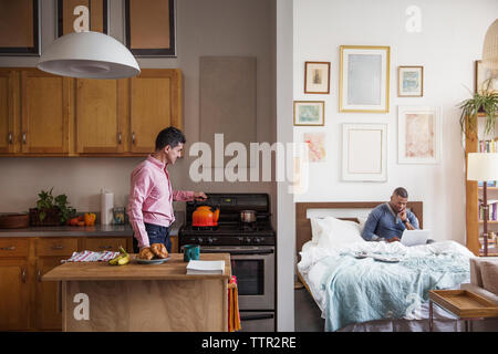 Homosexual man making coffee while partner using laptop at home - Stock Photo