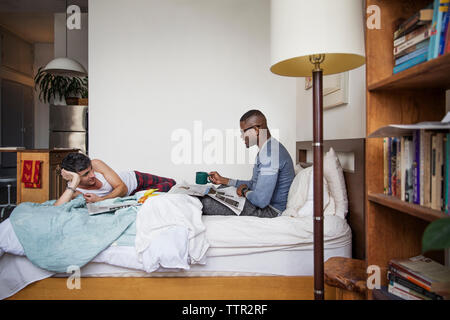 Gay men talking while reading newspaper in bedroom - Stock Photo