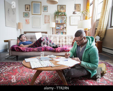 Homosexual man drawing while partner using laptop at home - Stock Photo