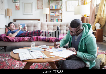Homosexual man drawing while partner using tablet computer at home - Stock Photo
