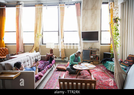Homosexual man drawing while partner using tablet computer in living room - Stock Photo