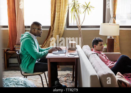 Side view of gay man using laptop at table while partner sitting on sofa - Stock Photo