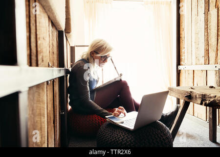 Young businesswoman using laptop while sitting on ottoman at office - Stock Photo