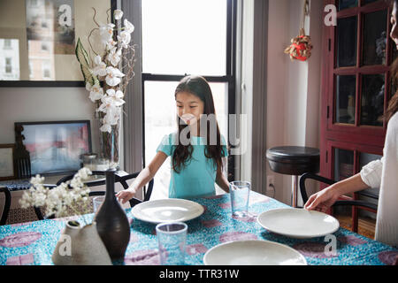 Happy sisters arranging plates on dining table at home