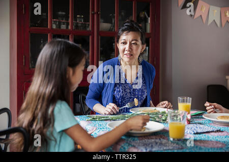 Mother talking to daughter while eating breakfast on birthday - Stock Photo