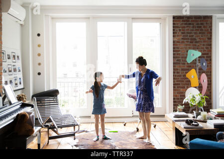 Girl and mother holding hands and dancing on carpet at home - Stock Photo