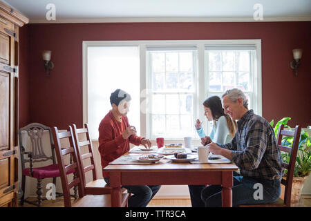 Happy family eating breakfast at table in home - Stock Photo