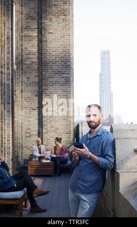 Portrait of man using mobile phone while colleagues sitting in background - Stock Photo