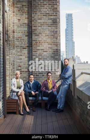 Portrait of business people in office balcony - Stock Photo