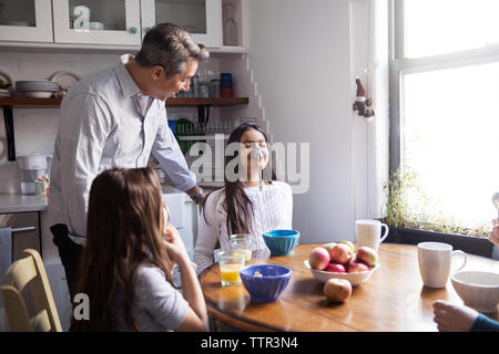 Father looking at girl balancing spoon on nose at table in kitchen - Stock Photo