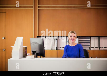 Portrait of smiling businesswoman sitting by desktop computer in office - Stock Photo