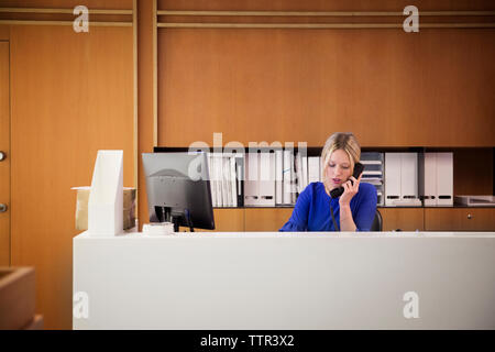 Businesswoman talking on telephone at desk in office - Stock Photo