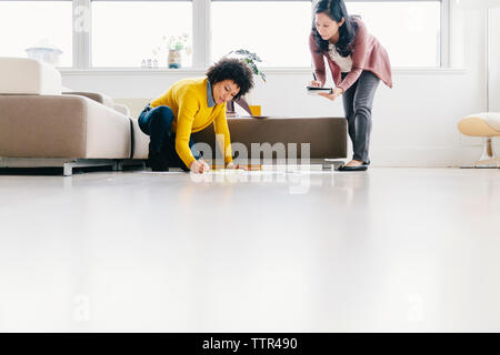 Surface level shot of businesswoman looking at female colleague writing on papers while kneeling in office - Stock Photo