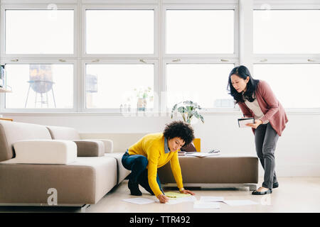 Businesswoman looking at female colleague writing on papers while kneeling in office - Stock Photo