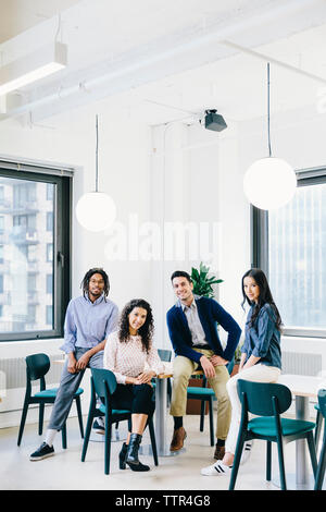 Portrait of smiling business people sitting in creative office - Stock Photo