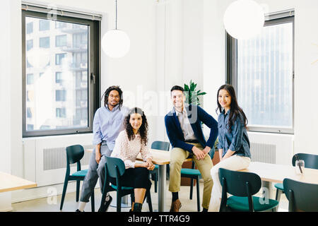 Portrait of confident business people sitting in creative office - Stock Photo
