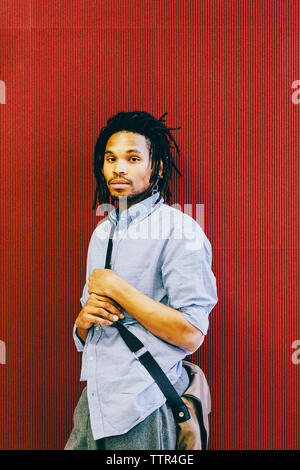 Portrait of confident businessman with messenger bag standing by red wall in creative office - Stock Photo