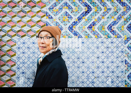 Portrait of senior woman wearing warm clothing standing against colorful tiled wall in city