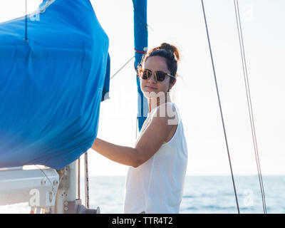 Side view portrait of confident mid adult woman standing on sailboat - Stock Photo