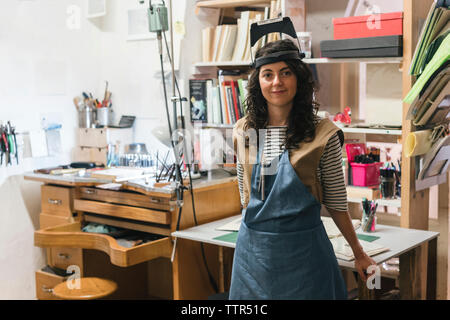 Portrait of confident female artisan standing by table in workshop - Stock Photo