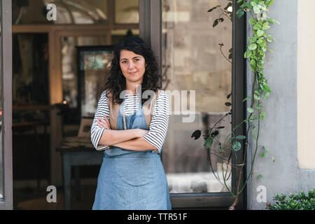 Portrait of confident female artisan with arms crossed standing by door at workshop - Stock Photo