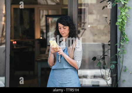 Confident female artisan using smart phone while standing by door at workshop - Stock Photo